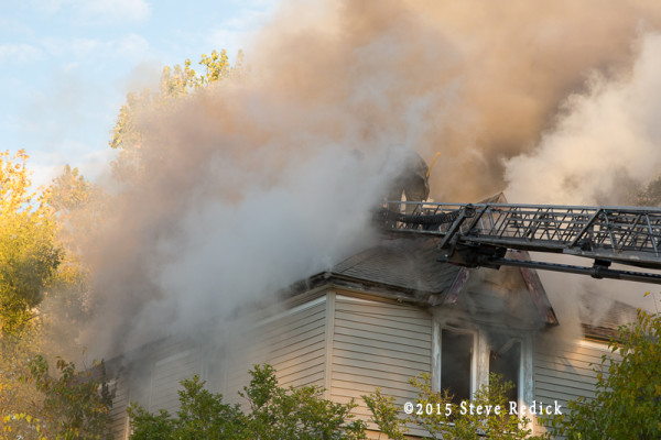 firemen vent house roof during fire