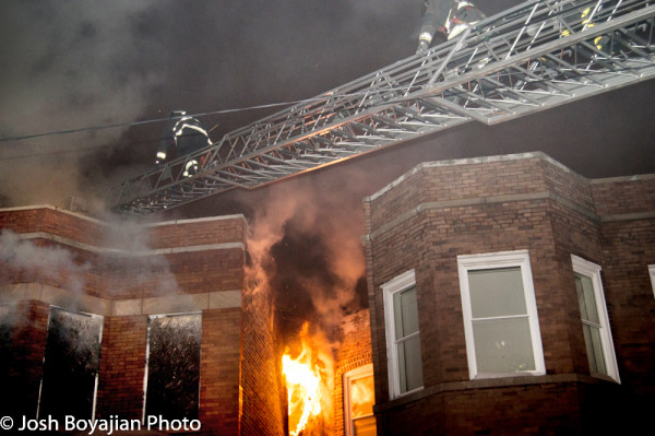 firemen climb aerial to roof during fire