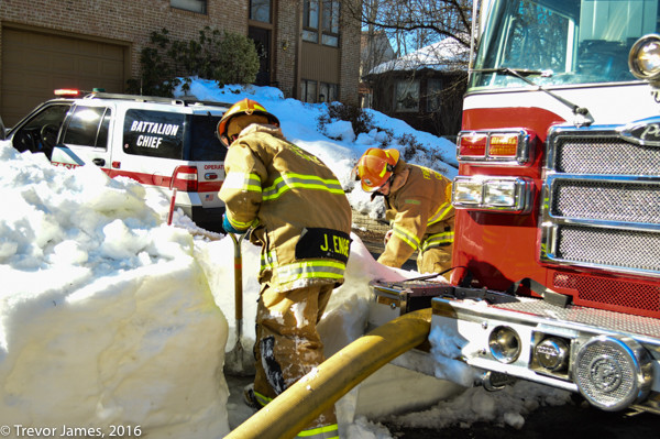 firefighters dig out fire hydrant covered with snow