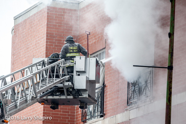 firemen in Pierce tower ladder platform