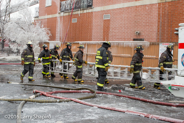 firemen carry frozen ladder