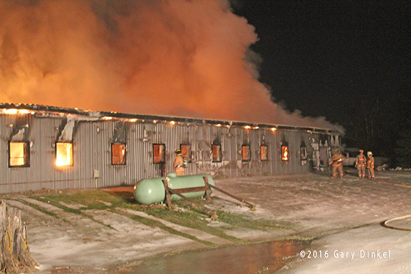 firefighters battle a horse stable fire at night in the winter
