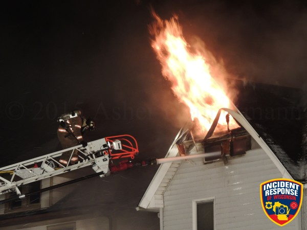 flames from attic of house at night