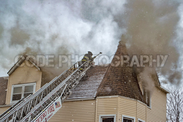 firemen vent roof at fire scene