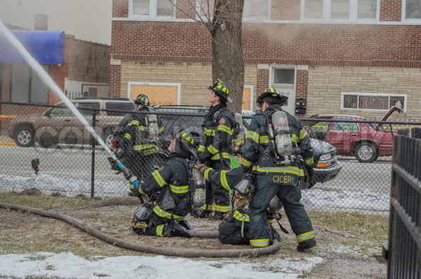 firemen with hose line at fire scene