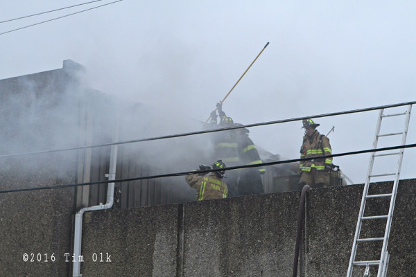 firemen on roof at fire scene