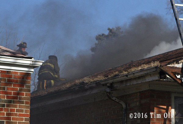 firefighter vents roof at house fire