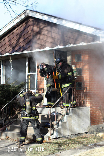 firefighters prepare to make entry at house fire