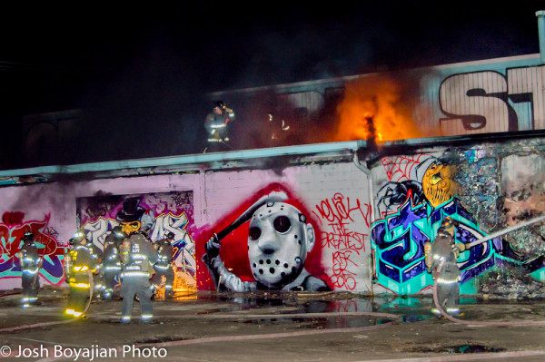 graffiti covered building on fire