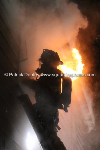 firefighter on ladder at night with flames