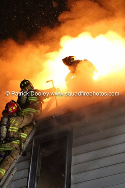 firefighters on roof of house at night with flames
