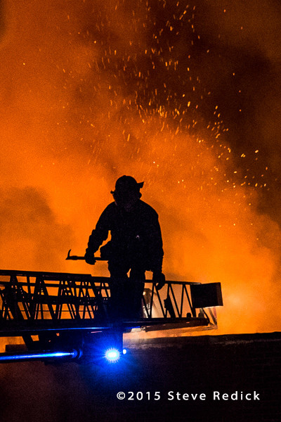 silhouette of fireman on aerial ladder