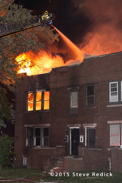 flames through the roof of a two-story building