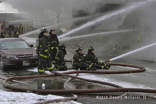 firefighters with hose lines at fire scene