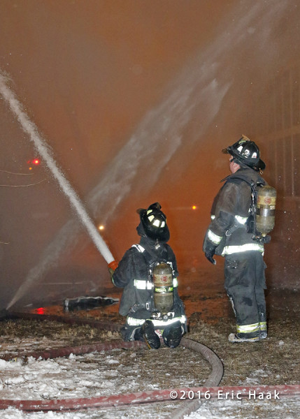 firemen with hose at fire scene