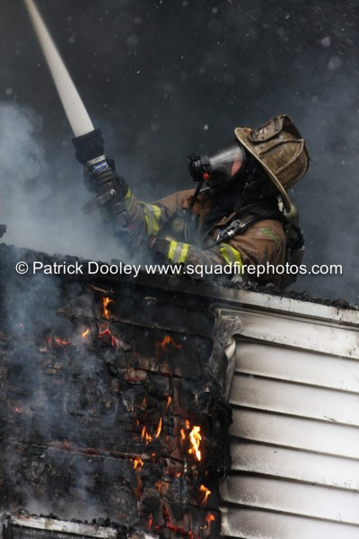 firefighter with PPE mask and hose line