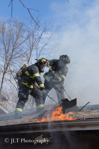 firemen on roof of house fire