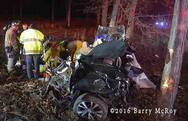 firefighters work to free the driver from a 2016 Nissan destroyed in crash