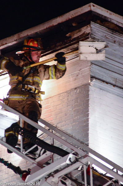 firefighter on ladder tip doing overhaul