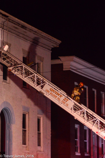 firefighter descends aerial ladder at night