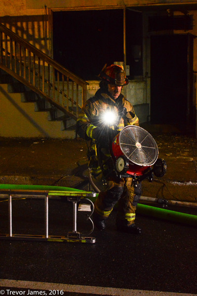 firefighter carrying a fan