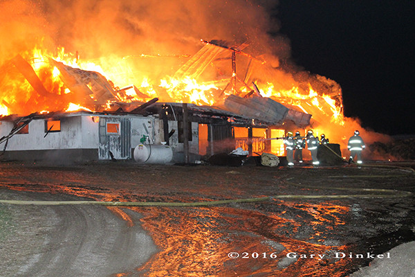 dairy barn fully engulfed in flames at night