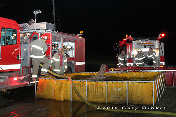 firefighters draft water from a portable tank at a rural fire scene