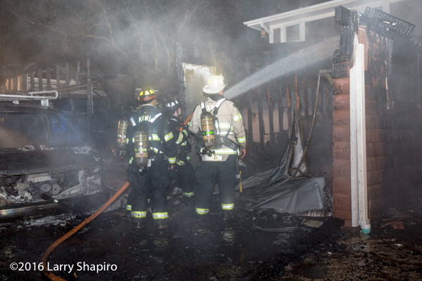 firefighters wash down the aftermath of a house fire in a rain storm