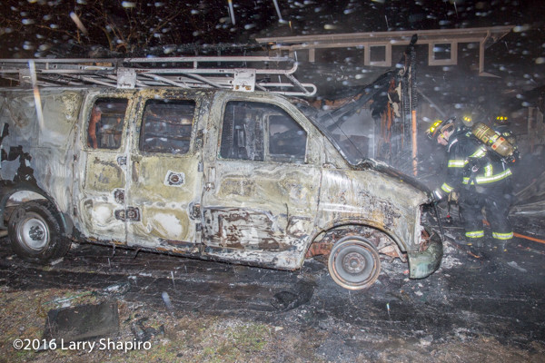 burned shell of a delivery van next to a house