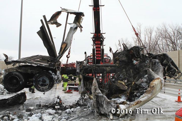 heavy wrecker tow truck from Ernie's Wrecker service lifts charred remains of a truck