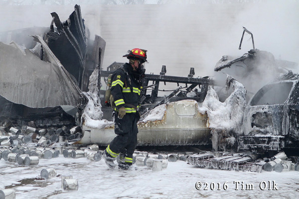firefighter walks through foam after truck fire