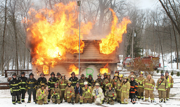 firefighters pose with burning house after training