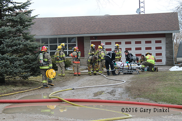 firefighters and EMS personnel attend to a victim of a house fire