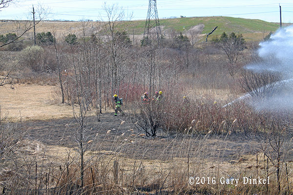 firefighters fight grass fire in urban area