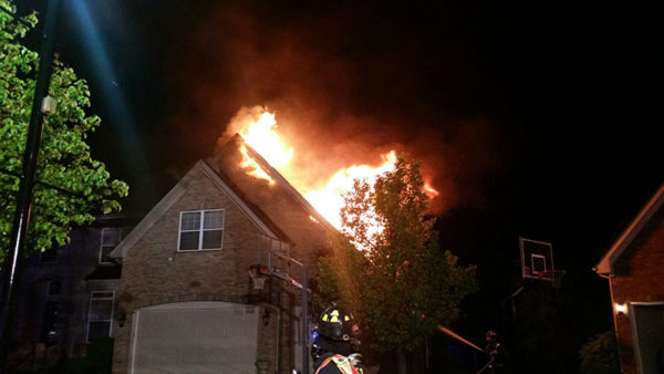 flames through roof of house at night