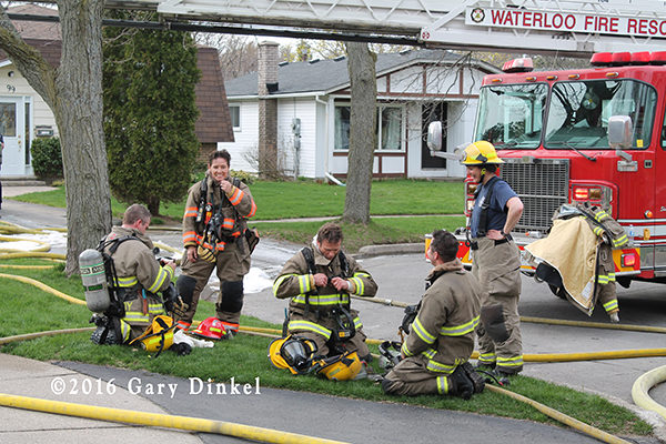 firefighters relax after a house fire in Waterloo Ontario