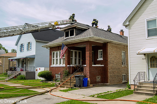 firemen on roof after house fire