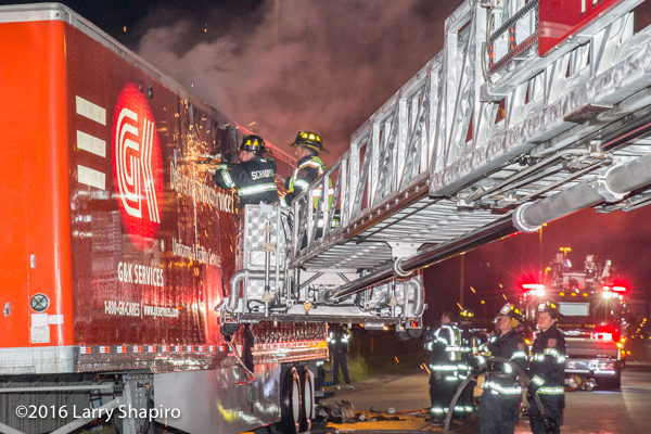 firemen use saw to cut semi trailer