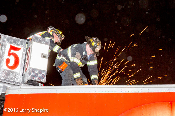 fireman uses a saw to cut semi trailer