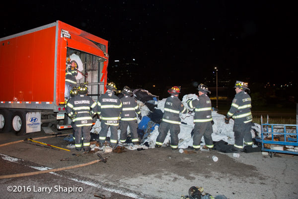 firemen overhaul truck contents after fire