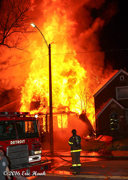 firefighter at fully engulfed house fire