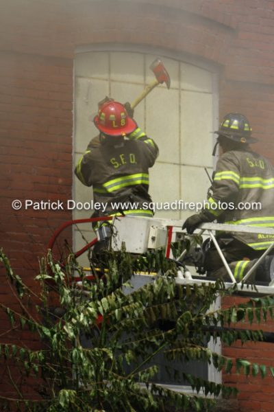 firefighters vent window from aerial ladder