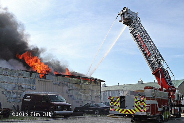 firefighters battle auto body shop fire