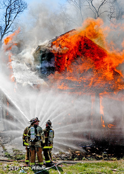 firemen creating a water curtain at a vacant house fully engulfed in flames