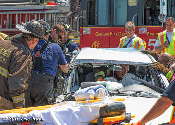 firefighters and paramedics extricate crash victim from car