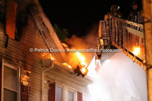 firefighters in tower ladder at night fire scene