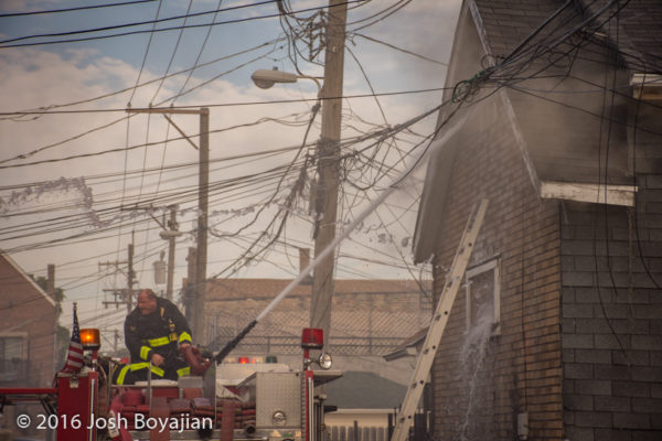 firefighter with deck gun at house fore