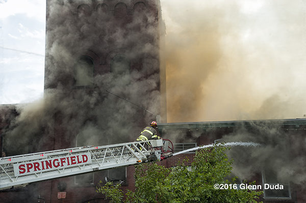 firefighter on aerial ladder tip at fire scene