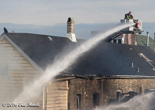 Chciago firefighters in tower ladder use master stream during a house fire