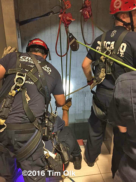 firefighters rescue trapped victims in an elevator